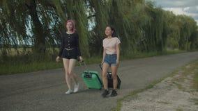 Los turistas de las mujeres con los bolsos del viaje caminan en el camino rural almacen de metraje de vídeo