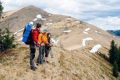 Los turistas de los amigos pasan el tiempo junto en las montañas imagenes de archivo