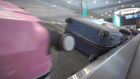 Los turistas del equipaje mienten en el carrusel de equipaje en el aeropuerto y esperan hasta que tomen a los dueños metrajes