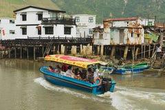 Los turistas disfrutan de viaje del barco en el pueblo de los pescadores del Tai O con las casas del zanco en Hong Kong, China Imagenes de archivo