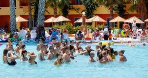 Los turistas el día de fiesta están haciendo aeróbicos de agua en piscina Fotos de archivo libres de regalías