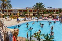 Los turistas el día de fiesta están haciendo aeróbicos de agua en piscina Foto de archivo