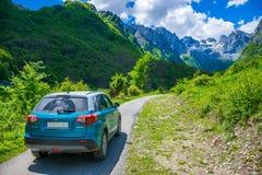 Los turistas en el coche de Suzuki Vitara fueron en un viaje a las montañas coronadas de nieve Fotos de archivo