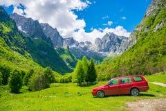 Los turistas en el coche de Suzuki Vitara fueron en un viaje a las montañas coronadas de nieve Imagen de archivo