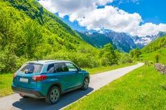 Los turistas en el coche de Suzuki Vitara fueron en un viaje a las montañas coronadas de nieve Imagen de archivo libre de regalías