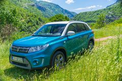 Los turistas en el coche de Suzuki Vitara fueron en un viaje a las montañas coronadas de nieve Imagenes de archivo