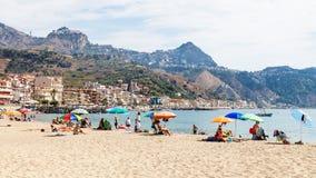 Los turistas en la arena varan en la ciudad de Giardini Naxos Fotos de archivo