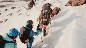 Los turistas en la expedici?n van uno tras otro con las mochilas grandes, con el equipo, ayud?ndose con los polos de esqu? almacen de video