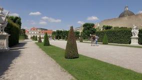 Los turistas están caminando en el jardín fabuloso del palacio del belvedere en la capital austríaca Viena almacen de metraje de vídeo