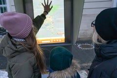 Los turistas estudian el mapa de Lviv en el invierno imágenes de archivo libres de regalías