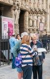 Los turistas estudian un mapa delante de la catedral de Notre Dame, París Fotos de archivo