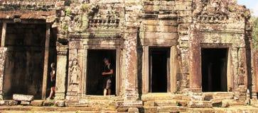 Los turistas exploran un templo en el complejo de Angkor, Camboya Foto de archivo libre de regalías