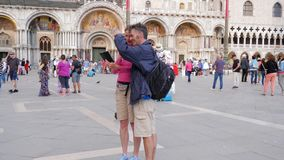 Los turistas felices con las mochilas hacen la foto en smartphone en el cuadrado de las marcas del St cerca de catedral almacen de video