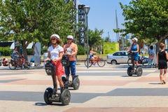 Los turistas felices se mueven en la playa de Barcelona con segway Foto de archivo