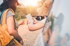 Los turistas femeninos investigan sobre direcciones de la gente en el ?rea para conseguir el objetivo correcto fotografía de archivo