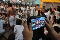 Los turistas fotografían una ceremonia del Taoist con la tablilla Imagenes de archivo