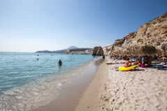 Los turistas gozan del agua clara de la playa hermosa de Firiplaka Foto de archivo