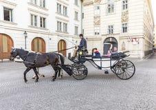 Los turistas gozan del carro traído por caballo o de Fiaker Imagen de archivo