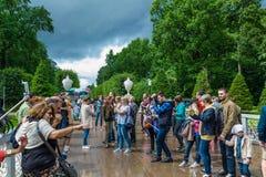 Los turistas hacen la foto en Peterhof, conocido para sus palacios y fuente Foto de archivo
