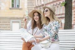 Los turistas hermosos de las muchachas están buscando una dirección en el mapa que se sienta en el banco Foto de archivo libre de regalías