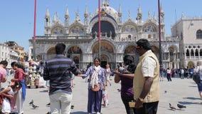 Los turistas hindúes con las palomas hacen la foto en el teléfono celular están en el fondo cuadrado de las marcas del St de la c almacen de video