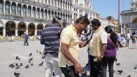 Los turistas hindúes fotografiados en los teléfonos móviles con las palomas están en el fondo cuadrado de las marcas del St de la almacen de video