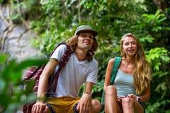 Los turistas jovenes de los pares están descansando sobre las rocas en la selva Imagenes de archivo