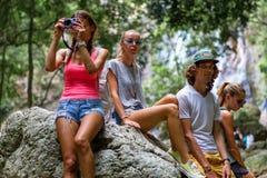 Los turistas jovenes están descansando sobre las rocas en la selva Foto de archivo