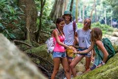 Los turistas jovenes están descansando sobre las rocas en la selva Fotografía de archivo libre de regalías