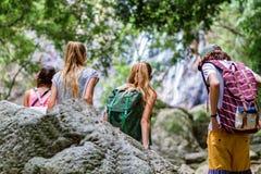 Los turistas jovenes están descansando sobre las rocas en la selva Imagen de archivo