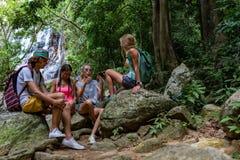 Los turistas jovenes están descansando sobre las rocas en la selva Imagen de archivo libre de regalías