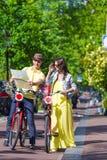 Los turistas jovenes juntan la mirada del mapa con las bicis adentro Fotos de archivo