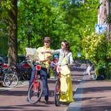 Los turistas jovenes juntan la mirada del mapa con las bicis adentro Fotografía de archivo