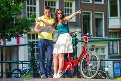 Los turistas jovenes juntan la mirada del mapa con las bicis adentro Imagenes de archivo