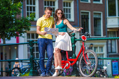 Los turistas jovenes juntan la mirada del mapa con las bicis adentro Imágenes de archivo libres de regalías
