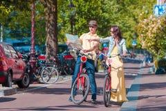 Los turistas jovenes juntan la mirada del mapa con las bicis en ciudad europea Imagen de archivo