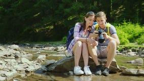 Los turistas jovenes miran las fotos capturadas en la cámara Se sientan en una roca cerca de un río de la montaña y de un bosque metrajes