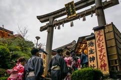 Los turistas junto con pueblo japonés en uniforme tradicional Imágenes de archivo libres de regalías