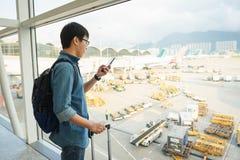Los turistas masculinos hermosos utilizan smartphones a los vuelos de control antes del embarque Uso del concepto del viaje de la fotografía de archivo