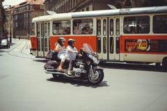 Los turistas mayores en una motocicleta montan abajo de la calle en Praga fotos de archivo