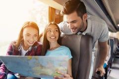Los turistas miran el mapa y eligen adonde ir después Discuten el viaje y la sonrisa próximos Imágenes de archivo libres de regalías