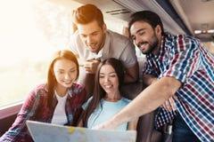 Los turistas miran el mapa y eligen adonde ir después Discuten el viaje y la sonrisa próximos Imagen de archivo libre de regalías