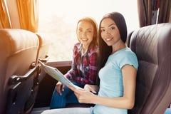 Los turistas miran el mapa y eligen adonde ir después Discuten el viaje y la sonrisa próximos Imagen de archivo
