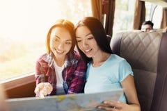 Los turistas miran el mapa y eligen adonde ir después Discuten el viaje y la sonrisa próximos Fotos de archivo