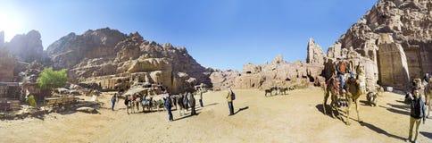 Los turistas montan en camellos cerca de las tumbas reales en el Petra Fotos de archivo libres de regalías
