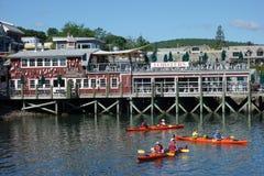 Los turistas montan los kajaks del mar en el puerto de la barra, Maine Foto de archivo libre de regalías