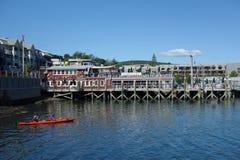 Los turistas montan los kajaks del mar en el puerto de la barra, Maine Imagen de archivo