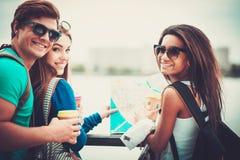 los turistas Multi-étnicos de los amigos con las tazas del mapa y de café acercan al río en una ciudad Fotografía de archivo