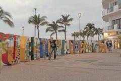 Los turistas pasan un Puerto Vallarta de tamaño natural firman adentro Puerto Vallarta, México fotos de archivo