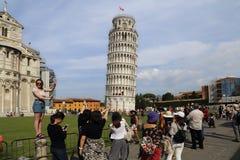 Los turistas presentan en la torre de Pisa, Italia Imagenes de archivo